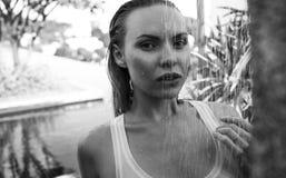 Sexig kvinna i bikinin och vitärmlös tröja som utomhus tar duschen på taket Arkivfoton