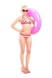 Sexig kvinna i bikinin som rymmer en simningcirkel Arkivbilder