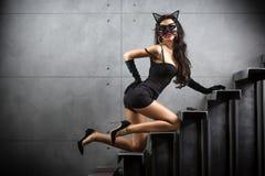 Sexig kvinna i catwomandräkten som ligger på trappa arkivbilder