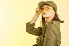 Sexig kvinna i dräkt för soldat` s på gul bakgrund Fotografering för Bildbyråer
