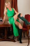 Sexig kvinna i en grön klänning med ett vinexponeringsglas Royaltyfri Foto