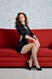 Sexig kvinna i ett kort svart klänningsammanträde på soffan Arkivbilder
