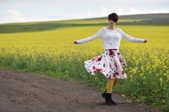 Sexig kvinna i kjoldans nära ett canolafält Arkivbilder
