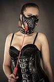 Sexig kvinna i korsett och maskering med grova spikar arkivbild