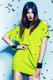 Sexig kvinna i near blå vägg för neongräsplanklänning Arkivfoto
