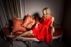 Sexig kvinna i röd klänning som lägger på den utsmyckade soffan Arkivfoto