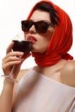 Sexig kvinna i rött dricka vin från ett exponeringsglas Royaltyfri Bild