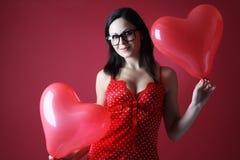 Sexig kvinna i röd damunderkläder med ballongformhjärta på röd bakgrundsvalentindag Arkivfoton