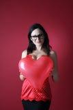 Sexig kvinna i röd damunderkläder med ballongformhjärta på röd bakgrundsvalentindag Arkivbilder