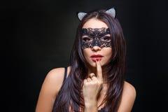 Sexig kvinna i svart damunderkläder och maskering på svart bakgrund royaltyfri foto