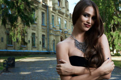 Sexig kvinna i svart klänning och halsband royaltyfri fotografi