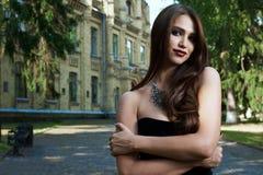 Sexig kvinna i svart klänning och halsband arkivfoto