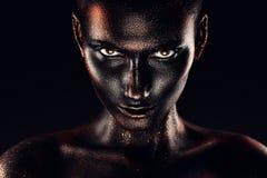 Sexig kvinna i svart målarfärg i mörker fotografering för bildbyråer