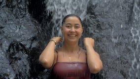 Sexig kvinna i tropiskt paradisanseende under vattenfallet som tycker om hennes semester på att förbluffa vattenfallet på tropisk arkivfilmer