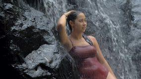 Sexig kvinna i tropiskt paradisanseende under vattenfallet som tycker om hennes semester p? att f?rbluffa vattenfallet p? tropisk lager videofilmer