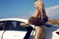 Sexig kvinna med blont hår i elegant klänning och päls som poserar bredvid en bil Royaltyfri Bild