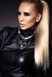 Sexig kvinna med blont hår i läderomslag och halsband royaltyfri fotografi