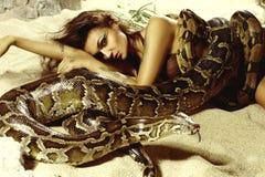 Sexig kvinna med en orm på stranden Royaltyfri Fotografi