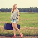 Sexig kvinna med en resväska royaltyfri bild