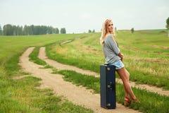 Sexig kvinna med en resväska fotografering för bildbyråer