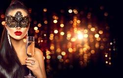Sexig kvinna med exponeringsglas av den bärande venetian maskeradmaskeringen för champagne arkivbild