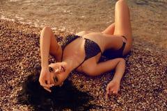 Sexig kvinna med mörkt hår i bikinin som ligger på stranden Royaltyfri Bild