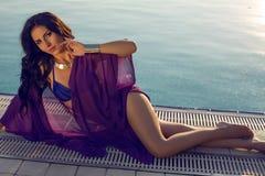 Sexig kvinna med mörkt hår i bikinin som poserar bredvid en simbassäng Royaltyfri Fotografi