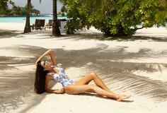 Sexig kvinna med mörkt hår i elegant bikini som kopplar av på Maldiverna Royaltyfria Bilder