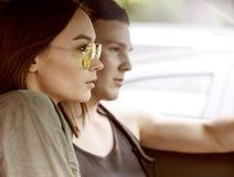 Sexig kvinna och man som kör en bil arkivfoto