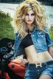 Sexig kvinna på en motorcykel Royaltyfria Bilder