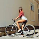 Sexig kvinna på stående för mode för fast kugghjulcykel en utomhus- royaltyfri foto