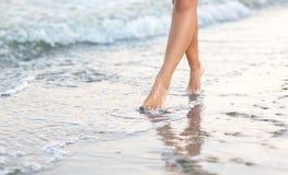 Sexig kvinna` s lägger benen på ryggen nära havet på sanden Härliga ben av en spenslig flicka Ben för sportkvinna` ett s Royaltyfri Fotografi