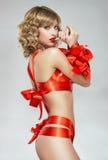Sexig kvinna som är destinerad med det röda gåvabandet Royaltyfria Bilder