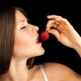 Sexig kvinna som äter jordgubben. Sinnliga röda kanter. Royaltyfri Bild