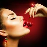 Sexig kvinna som äter körsbäret Fotografering för Bildbyråer