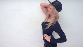 Sexig kvinna som bär den svarta läderhatten lager videofilmer
