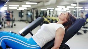 Sexig kvinna som gör en benpress i idrottshallen stock video