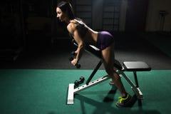 Sexig kvinna som gör genomkörare med hantlar i idrottshall Arkivfoton