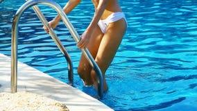 Sexig kvinna som klättrar en simbassängstege stock video