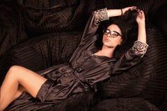 Sexig kvinna som ligger och poserar för kamera Bärande exponeringsglas och ämbetsdräkt för flicka Royaltyfri Foto