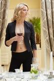 Sexig kvinna som poserar med exponeringsglas av vin i restaurang Fotografering för Bildbyråer