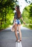 Sexig kvinna som promenerar vägen Arkivbild