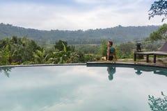 Sexig kvinna som tycker om solen på oändlighetssommarsimbassängen på den lyxiga semesterorten fotografering för bildbyråer
