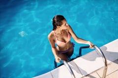 Sexig kvinna som tycker om sommar i pöl arkivfoton