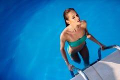 Sexig kvinna som tycker om sommar i pöl royaltyfri bild