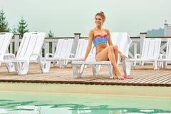 Sexig kvinna som tycker om sommarsemester nära pöl på semesterorten royaltyfria foton