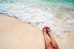 sexig kvinnasolbränna för härligt ben koppla av på den sandiga tropiska stranden Royaltyfri Foto