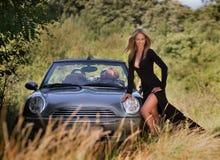 Sexig kvinnaställning nära till en cabrio i lång klänning Arkivfoton