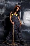 Sexig kvinnlig gruvarbetarearbetare med spetshackan, i overaller över hans nakna kropp arkivbilder