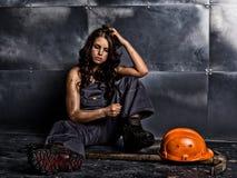 Sexig kvinnlig gruvarbetarearbetare med spetshackan, i overaller över hans nakna kropp erotiskt branschbegrepp royaltyfria bilder